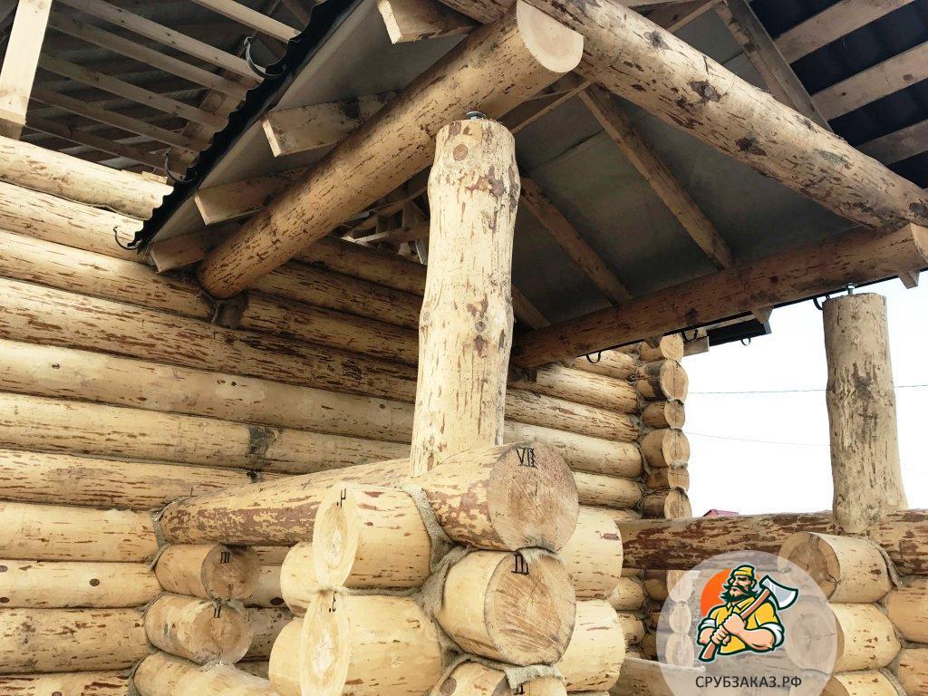 Сруб 6х9 из бревна ручной рубки с небольшой верандой на входе и высокой жилой мансардной крышей
